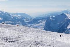Dos esquiadores cuesta abajo en cuesta y las montañas fuera de pista de la nieve en haz Imagenes de archivo