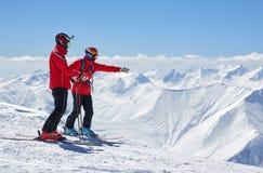 Dos esquiadores están en el borde de un acantilado en montañas Fotografía de archivo