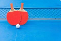 Dos estafas del ping-pong y bolas y redes en una tabla de ping-pong azul Imagenes de archivo