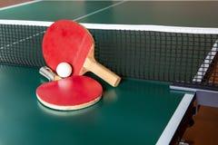 Dos estafas del ping-pong y una bola en una tabla verde Red del ping-pong imagen de archivo