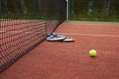 Dos estafas y bolas de tenis en corte Imágenes de archivo libres de regalías