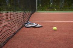 Dos estafas y bolas de tenis en un campo de tenis Fotos de archivo libres de regalías