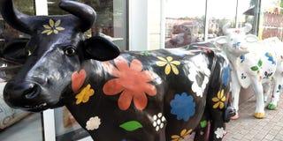 Dos estatuas de la vaca del cartón piedra con las flores pintadas delante de la carnicería foto de archivo