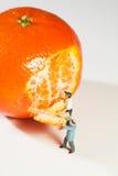 Dos estatuillas que pelan una naranja Imagenes de archivo