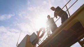 Dos estibadores, compañeros de trabajo y colleages hablando y sonriendo en un puerto industrial almacen de video