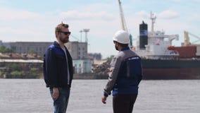 Dos estibadores, compañeros de trabajo y colleages resuelven y sacuden las manos en puerto del buque mercante almacen de metraje de vídeo