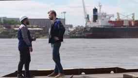 Dos estibadores, compañeros de trabajo y colleages sacuden las manos en puerto del buque mercante almacen de metraje de vídeo