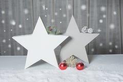 Dos estrellas con el abeto y conos que se colocan en nieve Fotografía de archivo