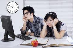 Dos estudiantes aburridos que estudian junto Foto de archivo