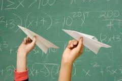 Dos estudiantes alrededor para lanzar los aviones de papel Imágenes de archivo libres de regalías