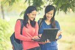 Dos estudiantes asiáticos jovenes que se unen, uno que sostiene un ordenador portátil Foto de archivo