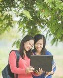 Dos estudiantes asiáticos jovenes que se unen, uno que sostiene un ordenador portátil Foto de archivo libre de regalías