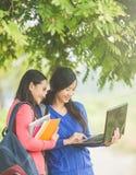 Dos estudiantes asiáticos jovenes que se unen, uno que sostiene un ordenador portátil Fotografía de archivo libre de regalías