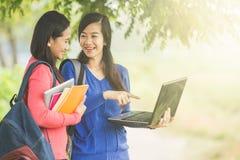 Dos estudiantes asiáticos jovenes que se unen, uno que sostiene un ordenador portátil Imagenes de archivo