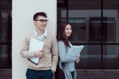 Dos estudiantes atractivos que hablan y que colocan el edificio exterior del campus Fotos de archivo