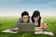 Dos estudiantes con el ordenador portátil en el campo Imágenes de archivo libres de regalías