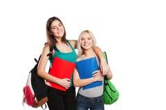 Dos estudiantes con la presentación de los bolsos de escuela aislados encendido Foto de archivo libre de regalías
