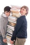 Dos estudiantes con los libros aislados en un blanco Imagen de archivo libre de regalías
