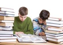 Dos estudiantes con los libros aislados en un blanco Fotografía de archivo libre de regalías