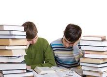 Dos estudiantes con los libros aislados en un blanco Imagenes de archivo