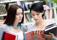 Dos estudiantes con los libros en la biblioteca Imagenes de archivo