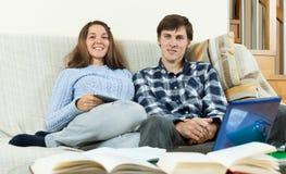 Dos estudiantes con los libros y el ordenador portátil que se sientan en el sofá Foto de archivo