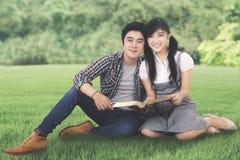 Dos estudiantes con un libro en el parque Fotografía de archivo