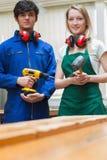 Dos estudiantes de la carpintería que se colocan antes de un banco de trabajo Fotografía de archivo libre de regalías