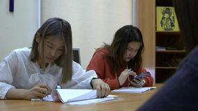 Dos estudiantes de la raza asiática en la tabla en la sala de clase almacen de video