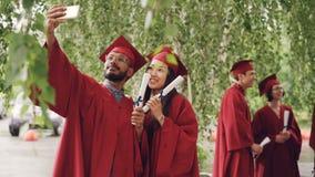 Dos estudiantes de la raza mixta están tomando el selfie con los diplomas de la graduación que llevan birretes y los vestidos, in almacen de video