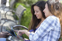 Dos estudiantes de la raza mixta que usan el ordenador de la almohadilla táctil afuera Imagen de archivo