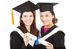 Dos estudiantes de tercer ciclo jovenes sonrientes que sostienen un diploma Imágenes de archivo libres de regalías