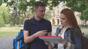 Dos estudiantes discuten algo en cuaderno en campus metrajes