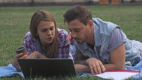 Dos estudiantes discuten algo en el ordenador portátil en el césped almacen de video