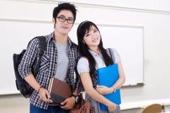 Dos estudiantes elegantes que se colocan en la clase Fotos de archivo