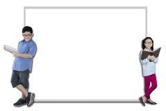 Dos estudiantes elementales que se inclinan en un whiteboard Imagen de archivo