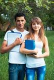 Dos estudiantes en parque con el libro al aire libre Imagen de archivo libre de regalías