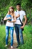 Dos estudiantes en parque con el libro al aire libre Fotografía de archivo libre de regalías