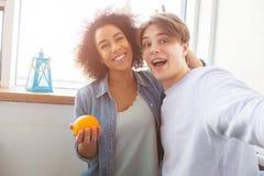 Dos estudiantes felices están tomando el selfie La muchacha está llevando a cabo una anecdotario anaranjada que sonríe mientras q Imagenes de archivo