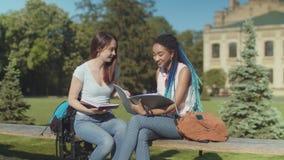 Dos estudiantes felices que charlan la sentada en banco almacen de metraje de vídeo