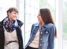 Dos estudiantes felices que hablan cerca de la ventana Foto de archivo