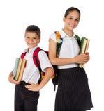 Dos estudiantes felices que se colocan con los libros en manos Imagen de archivo