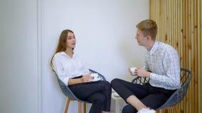 Dos estudiantes femeninos de la escuela secundaria que hablan llevando a cabo las bebidas que se sientan en un sofá en la sala de metrajes