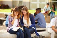 Dos estudiantes femeninos de la High School secundaria que trabajan en campus Imágenes de archivo libres de regalías