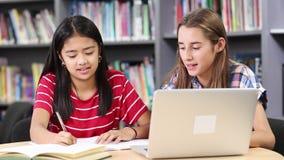 Dos estudiantes femeninos de la High School secundaria que trabajan en el ordenador portátil almacen de metraje de vídeo