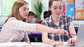 Dos estudiantes femeninos de la High School secundaria que trabajan en el ordenador portátil en sala de clase metrajes