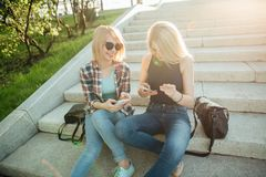 Dos estudiantes hermosos que miran el medios contenido en línea en teléfono elegante en parque Imagenes de archivo