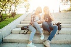Dos estudiantes hermosos que miran el medios contenido en línea en teléfono elegante en parque Fotografía de archivo libre de regalías