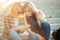 Dos estudiantes hermosos que miran el medios contenido en línea en teléfono elegante en parque Imágenes de archivo libres de regalías
