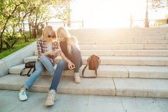 Dos estudiantes hermosos que miran el medios contenido en línea en teléfono elegante en parque Fotos de archivo